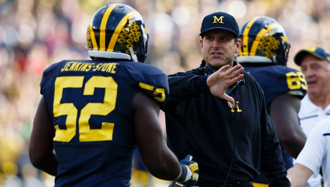 Michigan coach Jim Harbaugh congratulates linebacker Royce Jenkins-Stone during the Wolverines' 38-0 win vs. Northwestern on Saturday.