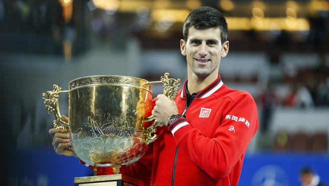 Novak Djokovic poses with trophies during the medal ceremony after the match against Rafael Nadal in the China Open.