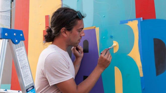Detroit-based artist Jesse Kassel live painted the Detroit Hustles Harder delivery truck during the Eastern Market After Dark event on Thursday, Sept. 24, 2015. Kassel is working on a Detroit-Windsor mural now.
