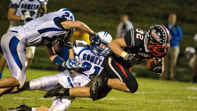 """West Branch's Luke Lenoch (32) gets tackled by Bellevue's Tyler Banowetz (23) and Noah Reed (21)  during the first half of play in West Branch at the """"Little Rose Bowl"""" on Friday, September 26, 2014. (Justin Torner/Freelance for the Press-Citizen)"""
