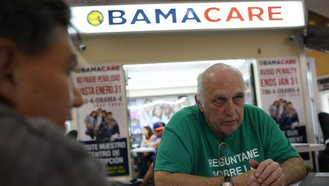 Joe Raedle,  Getty Images Miami insurance agent Antonio Galis, left, discusses Affordable Care Act plans with a client. UnitedHealth Group, the largest U.S. health insurer, said it may pull out of the Obamacare insurance exchange market.