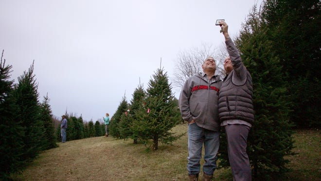 Andrea and Scott Carpenter, of Coshocton, take a selfie Wednesday evening at Scheetz Tree Farm after selecting a Christmas tree, their first tree after getting married.
