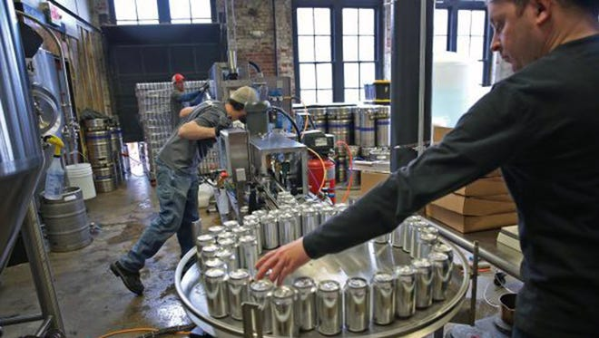 Brewer Nick Shadle of Indiana City Brewing Co., right, takes cans of freshly filled beer off the conveyor to weigh at the Indianapolis brewery Jan. 26, 2016.   iCan Solutions is a mobile canning company that serves brewers in four states.