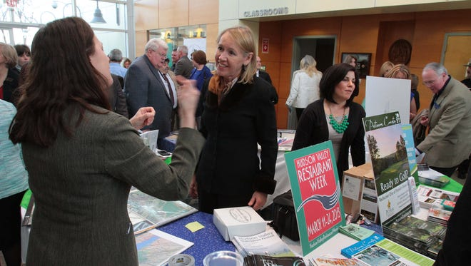 Putnam Tourism Director Libby Pataki, center, talks with guests attending an exhibition of county services and offerings from local businesses March 14,  2013.