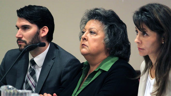 Former New Mexico Secretary of State Dianna Duran, center, is flanked by her legal team, attorney Erlinda Johnson, right, and legal assistant Travis Baggett during a hearing in Santa Fe on Oct. 8.