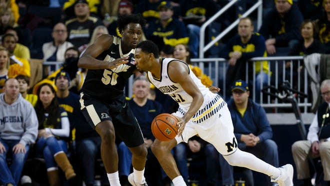 Michigan Wolverines guard Zak Irvin (21) moves the ball defended by Purdue Boilermakers forward Caleb Swanigan (50) in the second half at Crisler Center. Michigan won 61-56.