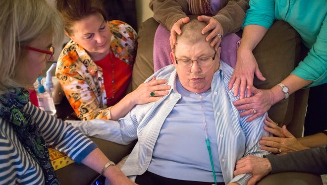 Joyce Hutchison receives prayers and comfort from friends during a prayer weekly circle at her condo in Des Moines on March 15, 2016. The hospice nurse who served the Des Moines community was diagnosed with lung cancer in 2013 and now receives in-home hospice care.