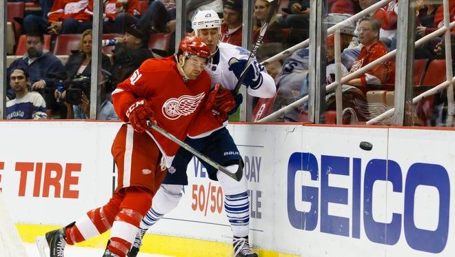 Detroit Red Wings defenseman Xavier Ouellet, left, checks Toronto Maple Leafs center Shawn Matthias on Oct. 2, 2015.
