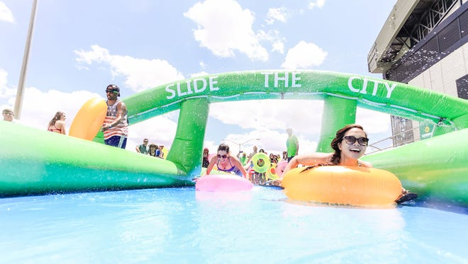 During Slide the City, participants slide through downtown Phoenix on a 1,000-foot- long slide.