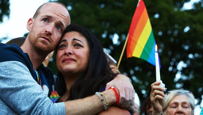Jeffrey Erikson and Jamie Fernandez hold each other during a moment of silence at a vigil in Cal Anderson Park in Seattle for the victims of a mass shooting at Pulse nightclub in Orlando, Fla., Sunday, June 12, 2016. (Genna Martin/seattlepi.com via AP) MAGS OUT; NO SALES; SEATTLE TIMES OUT; TV OUT; MANDATORY CREDIT