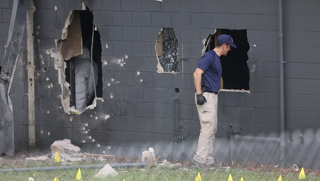 FBI agents investigate near the rear wall of the Pulse Nightclub where Omar Mateen allegedly killed at least 50 people on June 12, 2016, in Orlando.