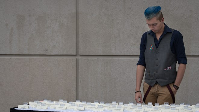 "Matther Lielke takes a final look at all of the candles before the vigil begins. A Community Vigil ""Remembering the Orlando Victims"" was held Thursday afternoon at UW-Oshkosh. The gathering was sponsored by The Office of Equity and Affirmative Action, the Division of Academic Support of Inclusive Excellence, and the LGBTQ Resource Center."