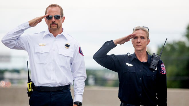 West Des Moines personnel salute the processional for the late Officer Shawn Miller as it drives down Interstate 35 in West Des Moines, Sunday, Aug. 7, 2016. Miller was killed in a motorcycle accident Aug. 3.