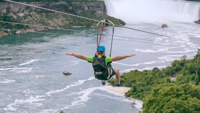 A tourist suspended above the water from zip lines makes his way across the Horseshoe Falls, on the Ontario side of Niagara Falls.
