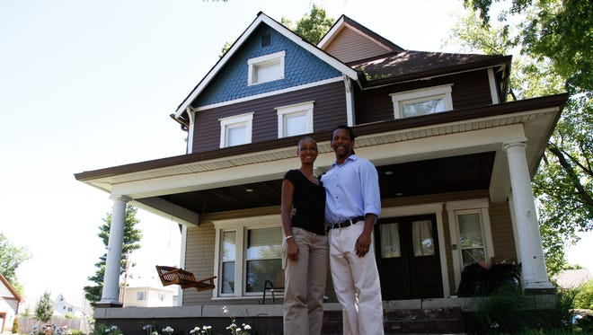 Carley and Troy Turner stand in front of the Fall Creek Place home. Their home sits on a street sprinkled with new homes, empty lots, and older homes.