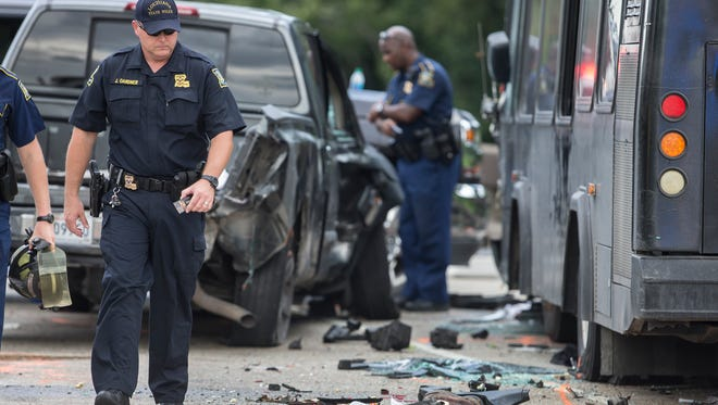 Police investigate the scene of a fatal wreck involving a bus and several cars on Interstate 10 near Laplace, La., Sunday.