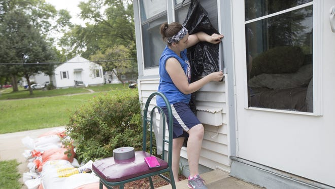 Sara Johnson of Cedar Rapids helps cover windows at a home in preparation for rising floodwaters in Cedar Rapids, Sunday, Sept. 25, 2016.