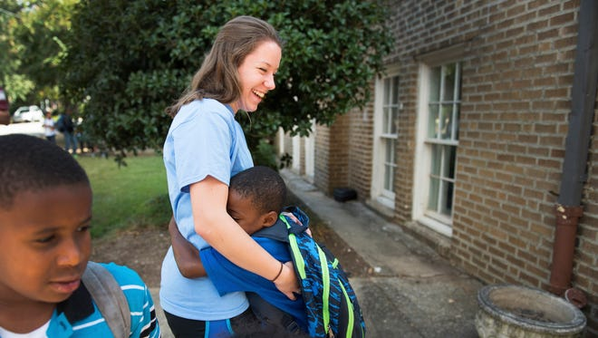 Lizzie Francis, a senior at Furman, gets a hug from London Gordon, 7, as he arrives at the Frazee Dream Center in Greenville on Tuesday, October 4, 2016.
