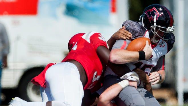Huntingdon's Parker Allen (40) and Trey Hayes (33) tackle LaGrange quarterback Connor Blair (15) at the Huntingdon campus on Saturday, October 15, 2019.