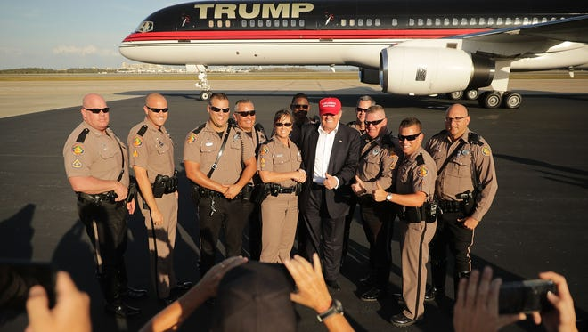 ORLANDO, FL - GOP presidential nominee Donald Trump poses with law enforcement officers on the tarmac at Orlando International Airport Wednesday.