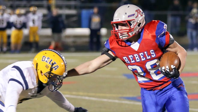 Roncalli RB Kenny Gillum stiff arms a Delta defender during the Rebels' 42-7 win Friday night in regional action.