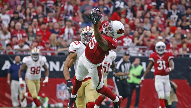 Arizona Cardinals wide receiver Michael Floyd (15) makes a catch behind San Francisco 49ers free safety Eric Reid (35) to set up a touchdown in the first quarter of their NFL game Sunday, Nov. 13, 2016 in Glendale,  Ariz.