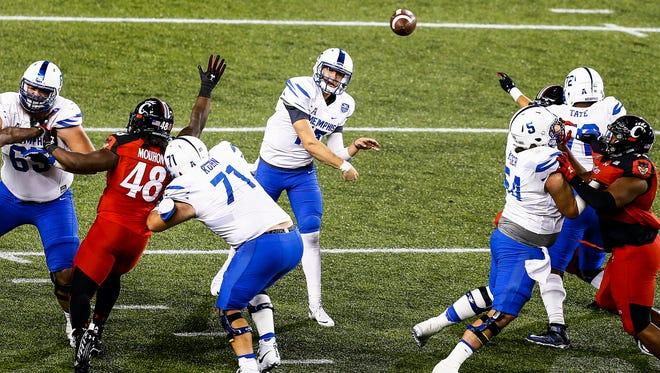 University of Memphis backup quarterback Jason Stewart (middle) throws a first down pass against the University of Cincinnati defense during fourth quarter action in Cincinnati, Ohio. Stewart, who replaced injured starting quarterback Riley Ferguson, finished the game completing 13 of 15 attempts for 138 yards and two touchdowns.