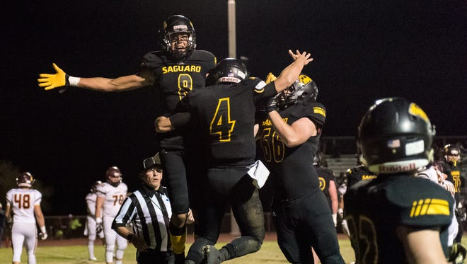Saguaro's Donovan Dalton (#8) and Nathan Sawyer (#66) celebrate with Max Massingale (#4) after his first quarter touchdown in the first quarter of the Division 4A semifinal playoffs on Friday, Nov. 18, 2016, at Desert Mountain High School in Scottsdale, Ariz.