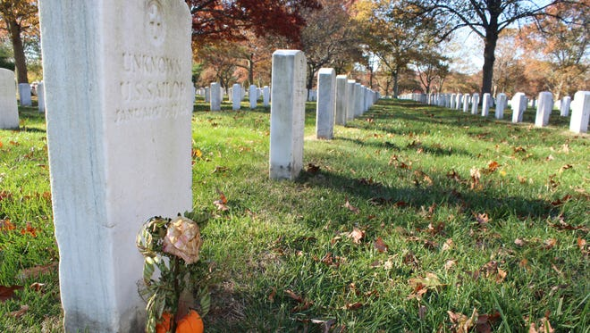 In this Nov. 11, 2016 photo, a gravestone, left, with the inscription UNKNOWN U.S. SAILOR, is adorned with a flower and a small pumpkin at Long Island National Cemetery in Farmingdale, N.Y.