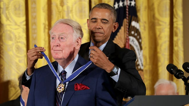 President Barack Obama awards the Presidential Medal of Freedom to broadcaster Vin Scully.