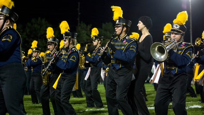 Alexandra Allers, 16, plays the clarinet and does formations along with her paraprofessional Kelsey Killian during halftime of a football game Oct. 7, 2016 at Memorial Stadium in Port Huron.