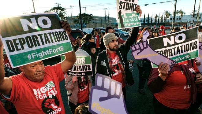 "Protesters carrying signs and chanting slogans march during a protest in downtown Los Angeles on Tuesday, Nov. 29, 2016. A few dozen protesters blocked a downtown Los Angeles intersection as part of a national wave of demonstrations in support of higher wages and workers' rights. Police stood by as the peaceful demonstrators formed a circle in the street early Tuesday while hoisting signs saying ""the whole world is watching"" and ""Fight for $15."""