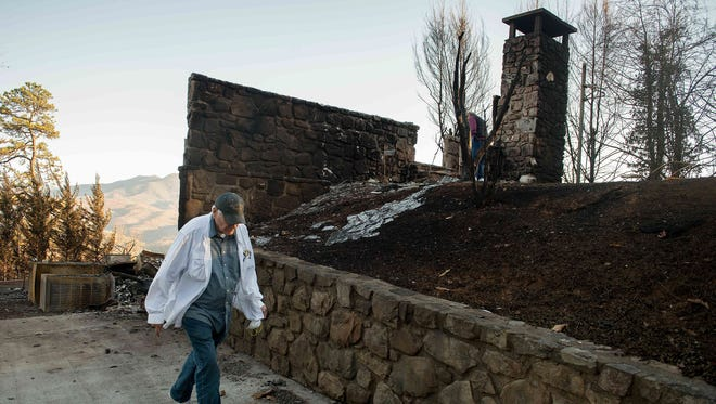 On Dec. 1, 2016, three days after wildfire, Richard T. Ramsey looks over the remains of the house he had lived in for 41 years in Gatlinburg, Tenn.