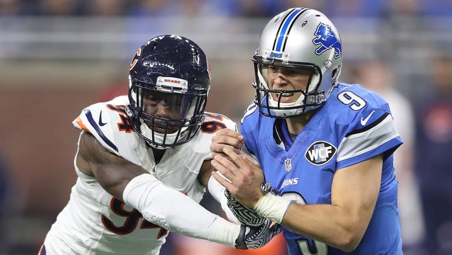 Matthew Stafford winces as he injures his right hand Sunday against Leonard Floyd and the Bears.