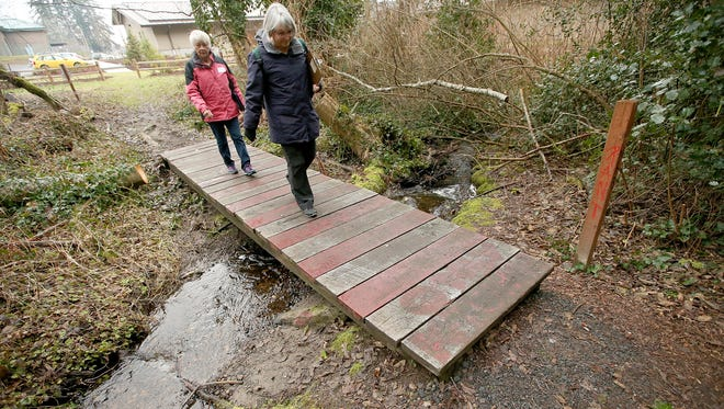Point In Time Count volunteers Barb Prentice (left), of Bremerton, and Kathy Caldwell, of Indianola, cross a small foot bridge Thursday as they enter the trail system behind the Village Green Community Center in Kingston.