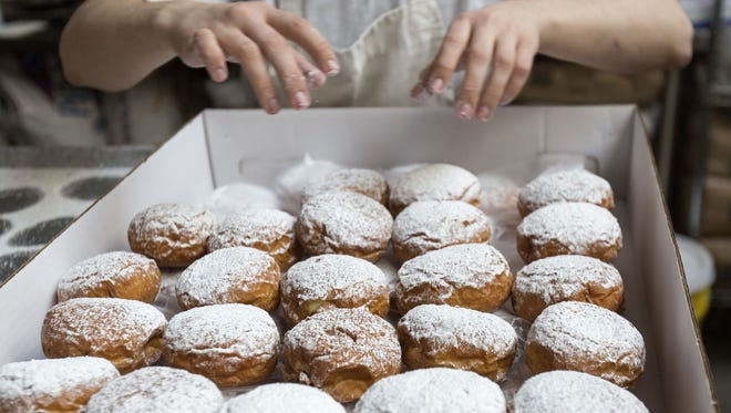 Sunca Bakic of Shelby Township, Mich., places freshly baked pączki into a box at New Martha Washington Bakery in Hamtramck, Mich.