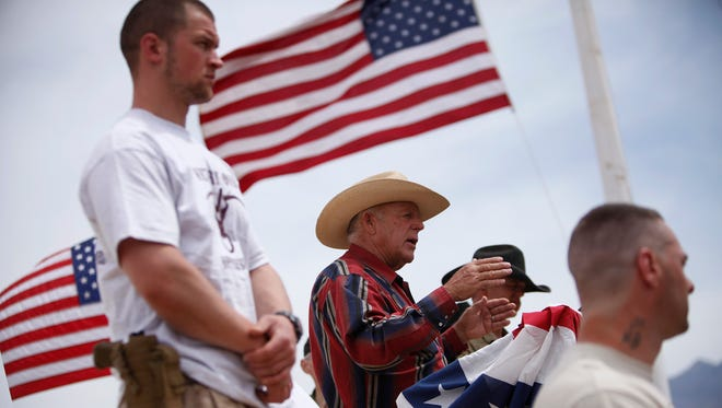 In this April 18, 2014, file photo, rancher Cliven Bundy, flanked by armed supporters, speaks at a protest camp near Bunkerville, Nevada.