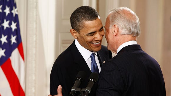 President Barack Obama (L) is embraced by Vice President