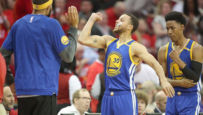 Golden State Warriors guard Stephen Curry high fives a teammate before playing against the Houston Rockets at Toyota Center.