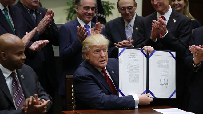 President Trump holds up the Veterans Choice Program And Improvement Act with VA Secretary David Shulkin clapping behind him, center, at the White House on April 19, 2017.