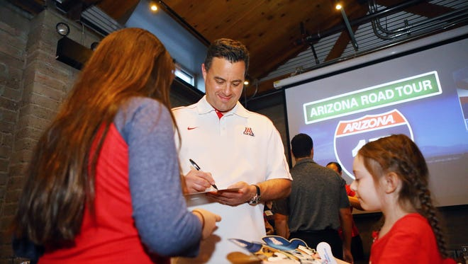 Sisters Gabi 12, and Emma 6, Higurea get an autograph from University of Arizona Head Basketball Coach Sean Miller during the Arizona Road Tour Wednesday, May 3, 2017 in Tempe, Ariz.