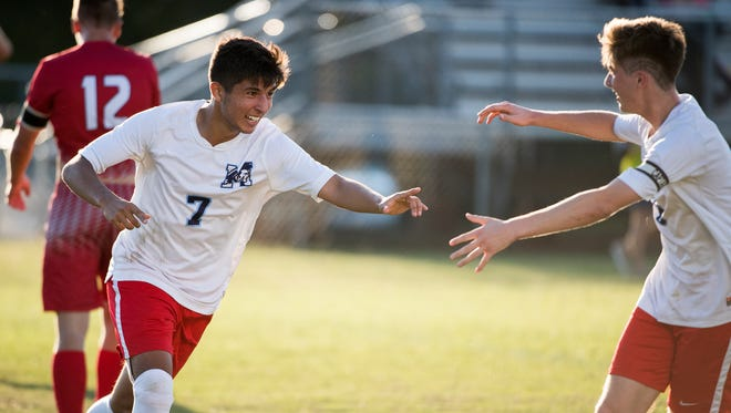 Mann's Nassim Al-Nawasreh (7) celebrates with teammate Quinn McNeill (8) after scoring a goal against Wade Hampton during a playoff match at J.L. Mann on Tuesday, May 9, 2017.