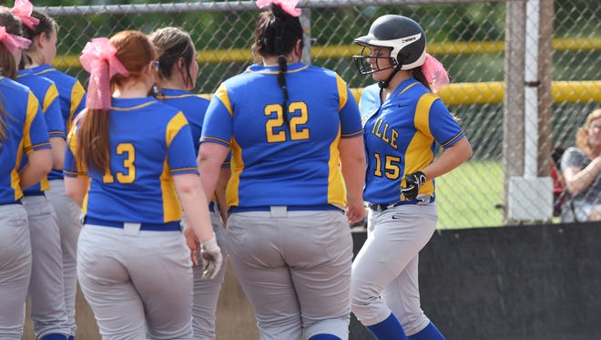Maysville's Rylei Miller disappears into a crowd of her teammates around home plate after hitting a two-run home run against Dover.