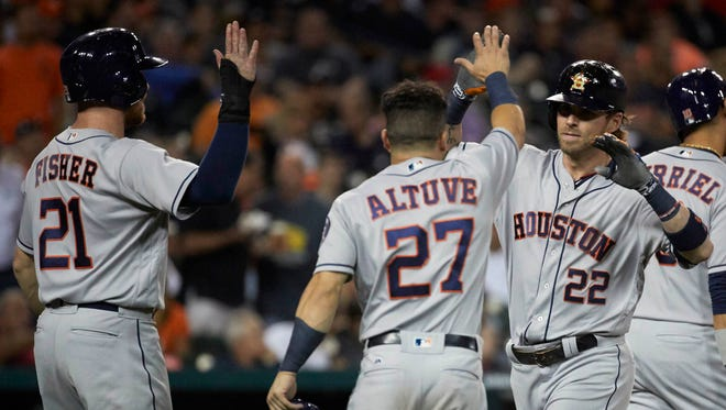 The Astros' Josh Reddick is congratulated by teammates Derek Fisher, left, and Jose Altuve, middle, after his three-run home run in the eighth inning against the Tigers at Comerica Park in Detroit.