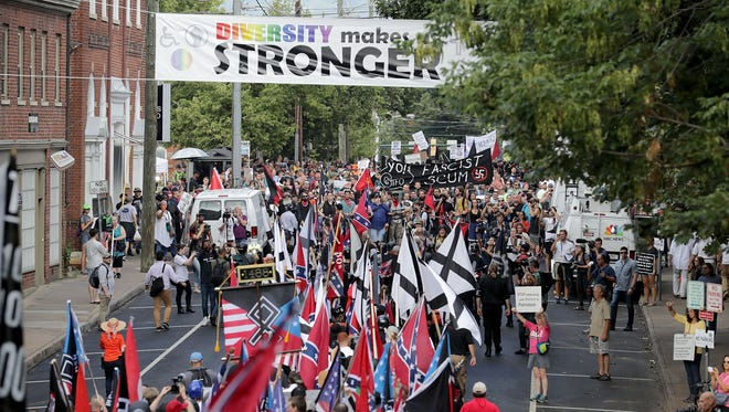 """Hundreds of white nationalists, neo-Nazis and members of the """"alt-right"""" march down East Market Street toward Lee Park during the """"United the Right"""" rally August 12, 2017 in Charlottesville, VA."""