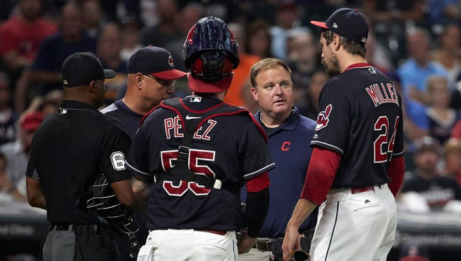 Indians reliever Andrew Miller is checked by, from left to right, umpire Alan Porter, manager Terry Francona, catcher Roberto Perez and a team trainer before leaving the game in the seventh inning with an injury against the Red Sox at Progressive Field. Mandatory Credit: Rick Osentoski-USA TODAY Sports