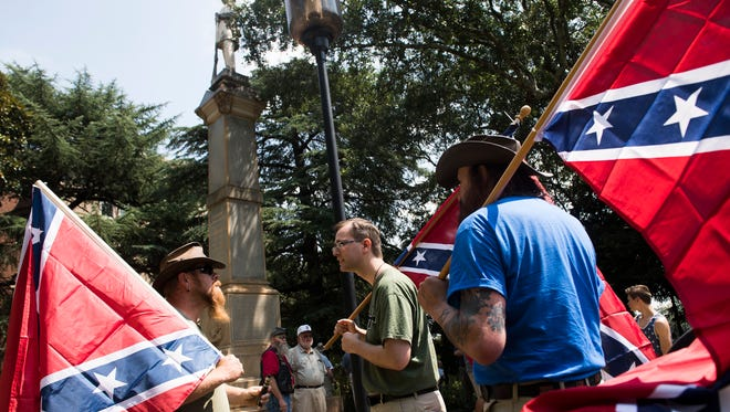 Supporters of the Confederate memorial on Main Street in Greenville arrive at the statue to counter-protest a group calling for its removal on Saturday, Aug. 26, 2017.