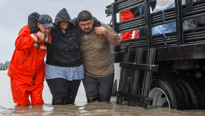 Volunteers and first responders work together to rescue residents from rising flood waters in Houston on Tuesday, Aug. 29, 2017.  Forecasters expect the storm to linger over the Gulf before heading back inland east of Houston sometime Wednesday. The system will then head north and lose its tropical strength.  (Scott Clause/The Daily Advertiser via AP)