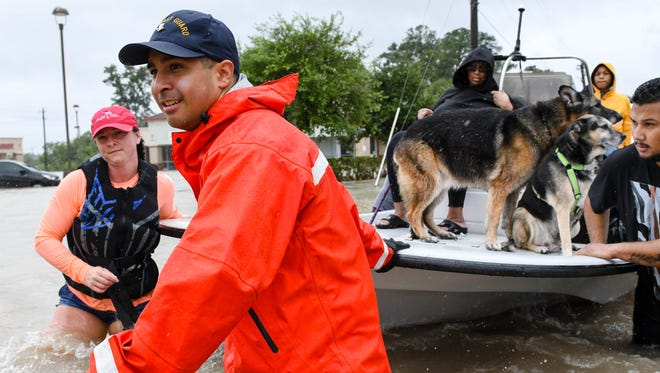 Volunteers and first responders work together to rescue residents from Hurricane Harvey's rising floodwaters in 2017.