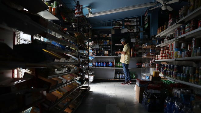 A person visits a store that doesn't have electricity two days after Hurricane Irma passed through the area on September 12, 2017 in Miami, Florida.